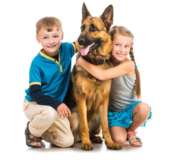 Young boy and girl kneeling down and holding their dog while smiling